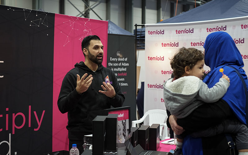 An image of Tenfold CEO Mohammad Quadan who is discussing the projects to a sister holding a young toddler