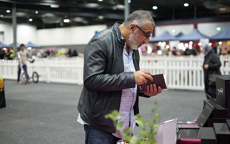 A man picks up and reads a Quran provided by Tenfold to donors for FREE