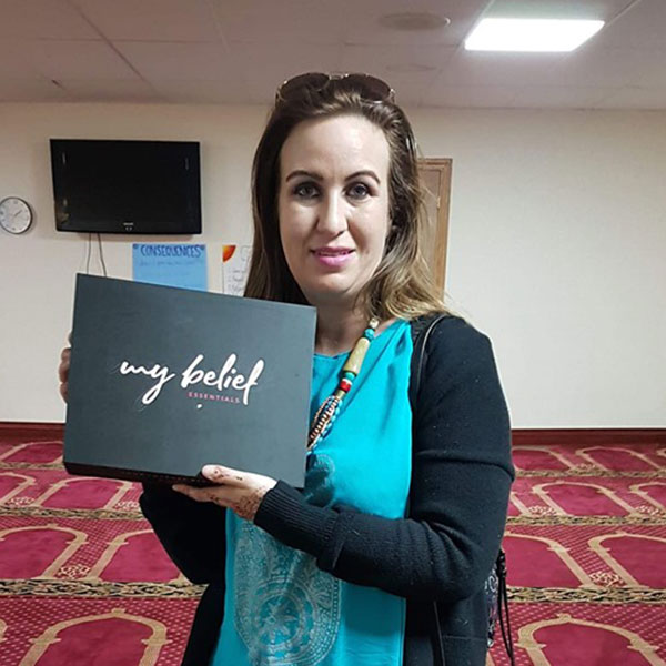 A picture of a New Muslim who after taking her shahada recieved a My Belief pack from Tenfold as a gift