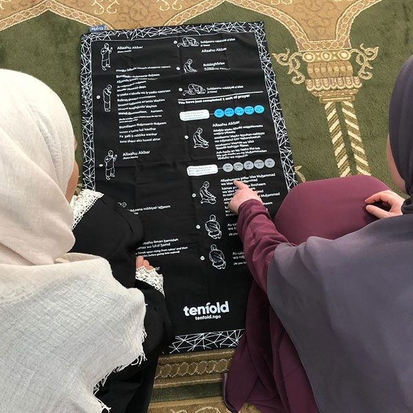 A muslim lady teaching another muslim who is a new muslim how to pray using the my prayer mat in Denmark