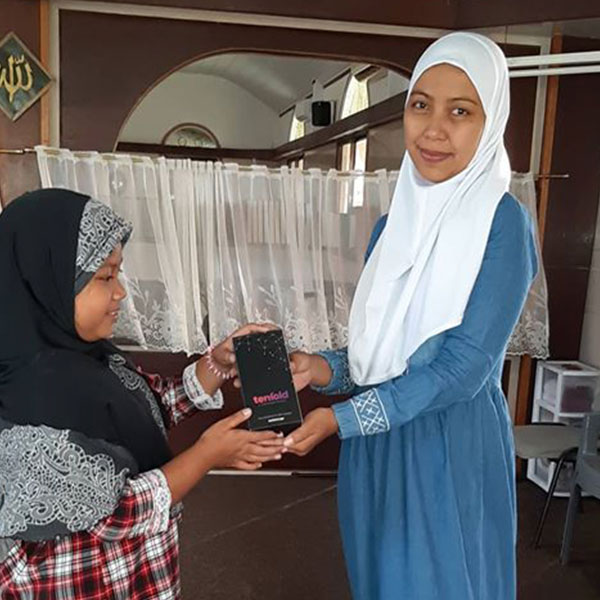 A new Muslim in the Suriname receives her Learn to pray pack from Tenfold gifted by the Muslim community in Suriname