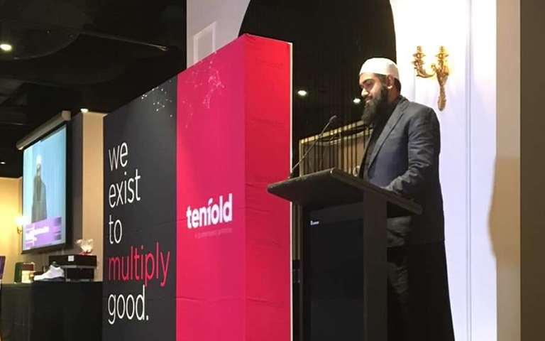 Sheikh Akram Buksh on stage speaking at the Tenfold Fundraising Dinner in 2018
