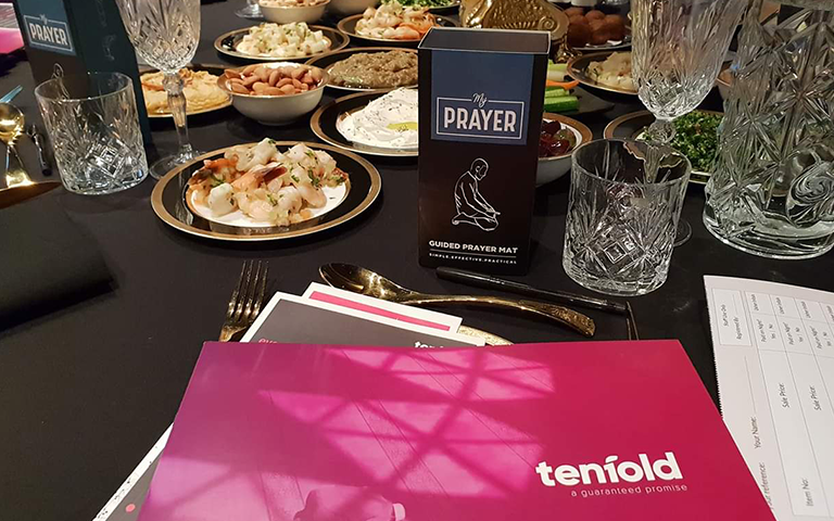 A my prayer pack displayed on the dressed table surrounded by gourmet food at the Tenfold Fundraising dinner along with the Tenfold portfolio