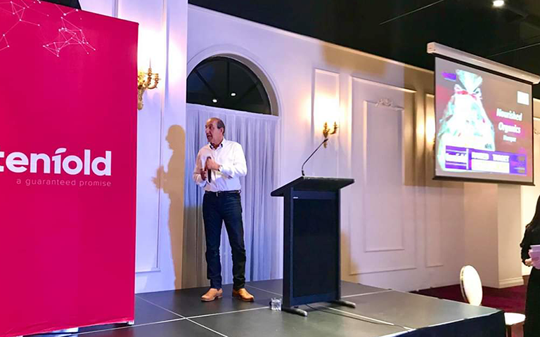 Hussin Goss on stage speaking at the Tenfold Fundraising Dinner in 2018